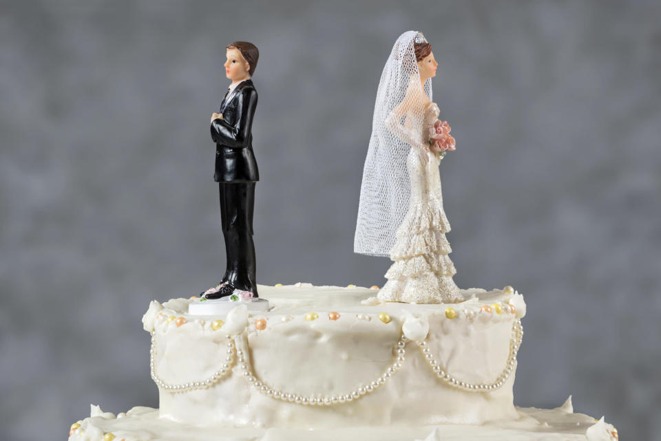 Wedding cake with bride and groom facing away from each other.