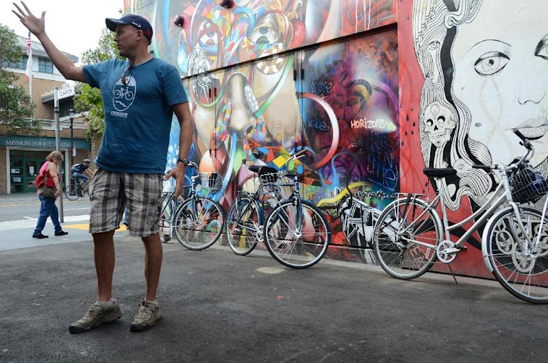 This October 2011 photo shows Streets of San Francisco Bike Tours guide and co-founder Eoin Canny explaining the history of mural art in the Mission District during a tour in San Francisco. Streets of San Francisco Bike Tours, launched in early 2011 by a group of friends who are passionate about both San Francisco and bicycles, and who'd worked as travel guides internationally before returning home to lead their own tours. (AP Photo/Paula Froke)