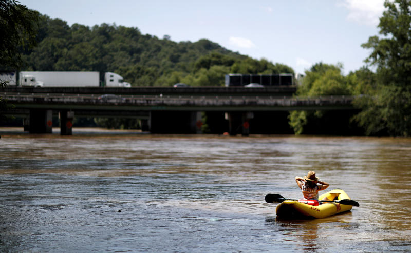 "FILE - This June 27, 2018 file photo shows a kayaker floating down the Chattahoochee River as traffic spans Interstate 285 in Atlanta. The toe-tapping river song that rhymes Chattahoochee with ""hoochie coochie"" was one of the biggest hits of Alan Jackson's career, earning him two Country Music Association Awards and two Grammy nominations. (AP Photo/David Goldman, File)"