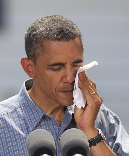 President Barack Obama wipes his face as he addresses supporters at the Wolcott House Museum in Maumee, Ohio, Thursday, July 5, 2012. (AP Photo/Carlos Osorio)