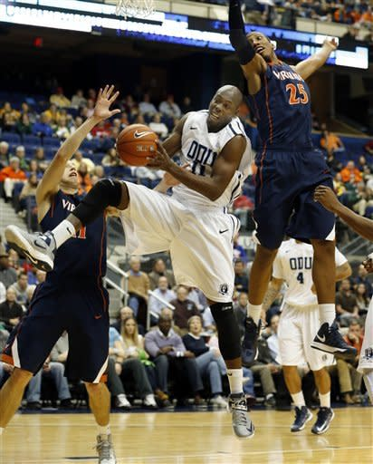 Old Dominion's DeShawn Painter (11) comes down with a rebound between Virginia defenders Evan Nolte, left,and Akil Mitchell, right, during first half action of an NCAA college basketball game in the 2012 Governor's Holiday Hoops Classic at The Richmond Coliseum in Richmond, VA.,Saturday,Dec.,22, 2012. (AP Photo/ The Richmond Times-Dispatch, Joe Mahoney)