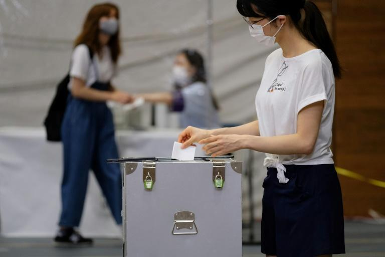 Voters in Tokyo were urged to use hand sanitiser after casting their ballot (AFP Photo/Kazuhiro NOGI)