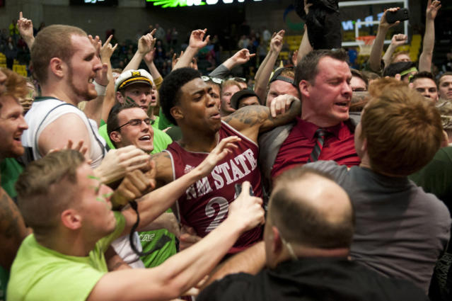 In this Thursday, Feb. 27, 2014 photo, New Mexico State's Daniel Mullings, center left in red and white jersey, is involved in a brawl involving players and fans who came onto the court when New Mexico State guard K.C. Ross-Miller hurled the ball at Utah Valley's Holton Hunsaker seconds after the Wolverines' 66-61 overtime victory against the Aggies in Orem, Utah. (AP Photo/The Daily Herald, Grant Hindsley)