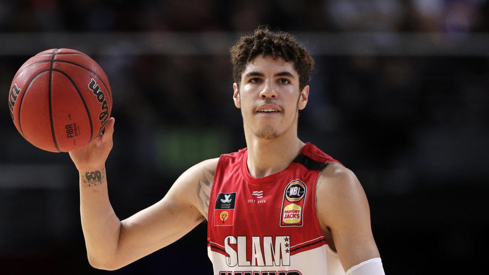 FILE - In this Nov. 17, 2019, file photo, LaMelo Ball of the Illawarra Hawks carries the ball up during their game against the Sydney Kings in the Australian Basketball League in Sydney.  LaMelo Ball's bone bruise on his left foot is expected to keep him out of the Illawarra Hawks lineup for the remainder of the National Basketball League season in Australia. The 18-year-old American, who joined Illawarra as part of the NBL's Next Stars program, is expected to be a first-round pick in this year's NBA draft.(AP Photo/Rick Rycroft, File)