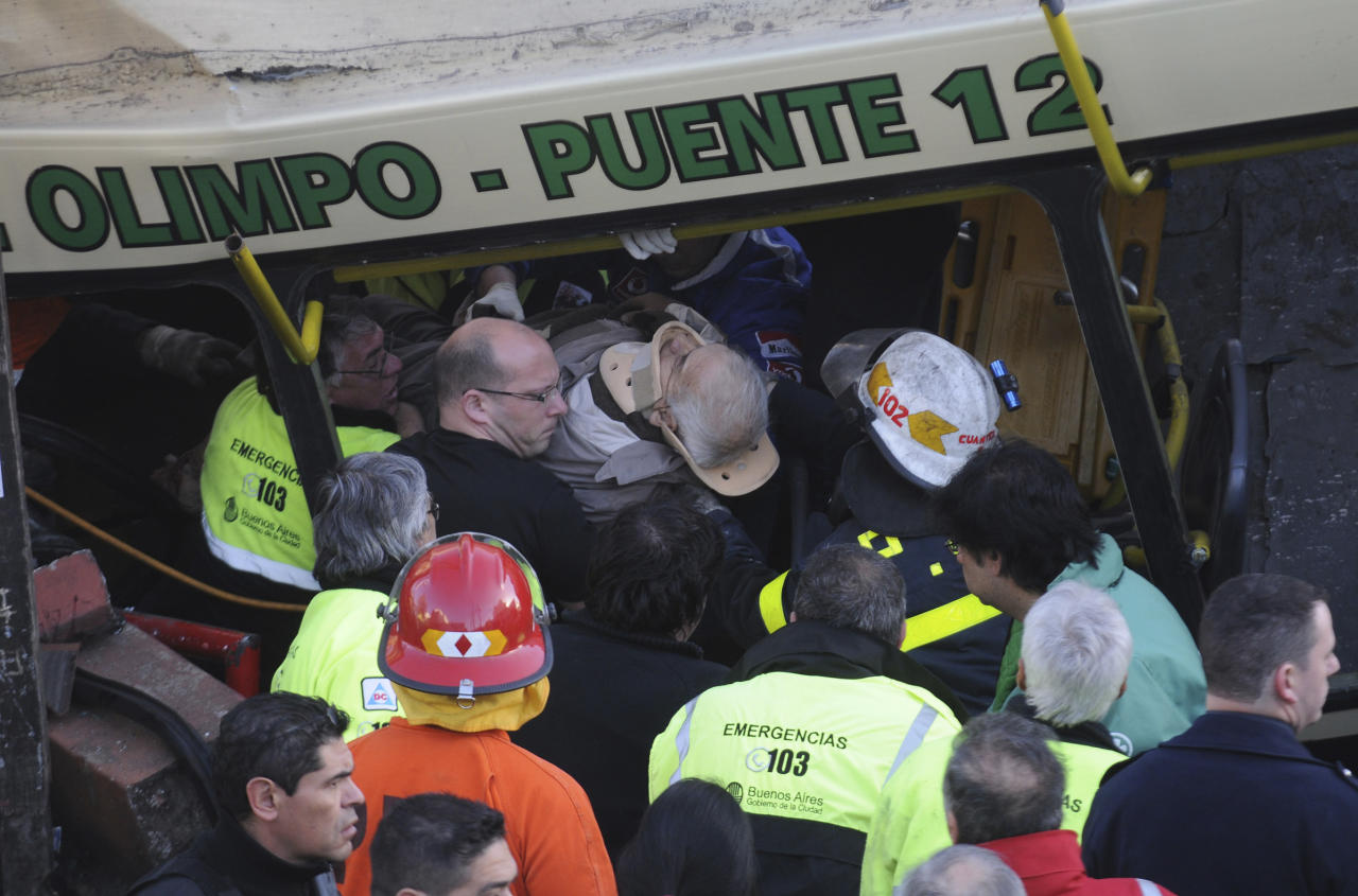 A wounded passenger is carried out a train after it crashed in Buenos Aires, Argentina, Tuesday, Sept. 13, 2011. At least seven people were killed and at least 162 injured in a rush-hour crash Tuesday involving two passenger trains and a bus whose driver drove around barriers in an attempt to beat them across the tracks, Argentine authorities said. (AP Photo/Rodolfo Pezzoni,DyN)