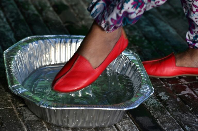 A woman disinfects the soles of her shoes before entering a supermarket during a break of the curfew imposed by the government against the spread of the new coronavirus, in the Honduran capital Tegucigalpa, on March 19, 2020