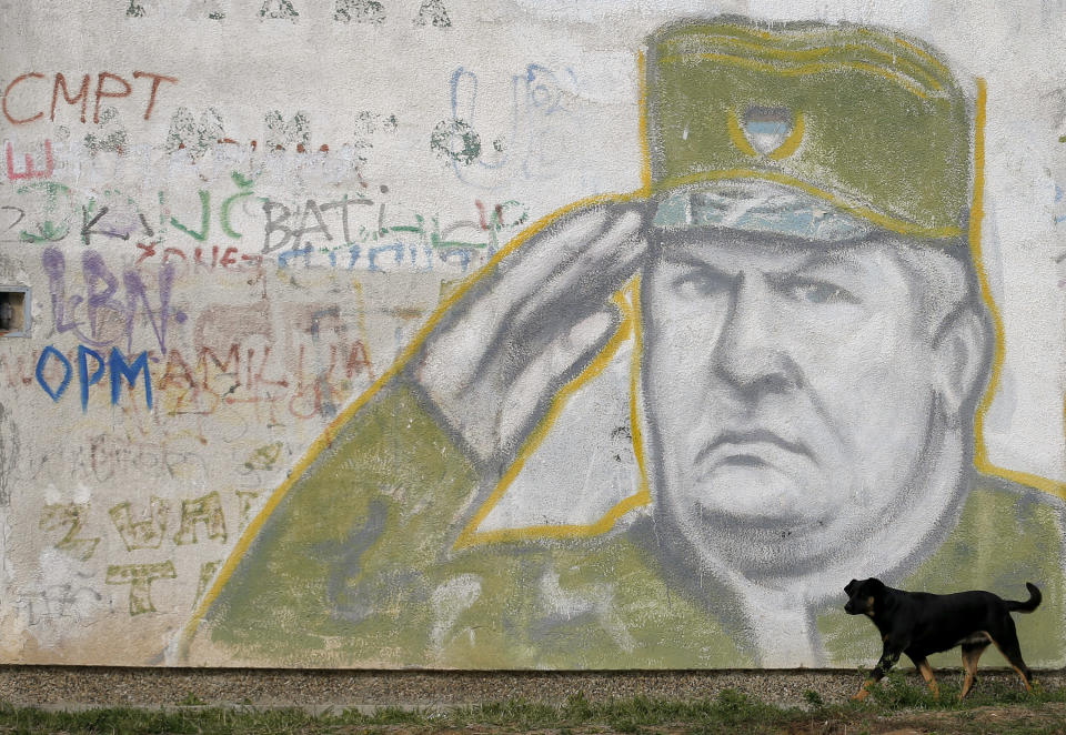 FILE — In this Tuesday, Nov. 7, 2017 file photo, a dog walks past a mural depicting former Bosnian Serb Gen. Ratko Mladic decorating a the wall of an apartment building in Belgrade, Serbia. U.N. judges on Tuesday, June 8, 2021 deliver their final ruling on the conviction of former Bosnian Serb army chief Radko Mladic on charges of genocide, war crimes and crimes against humanity during Bosnia's 1992-95 ethnic carnage. Nearly three decades after the end of Europe's worst conflict since World War II that killed more than 100,000 people, a U.N. court is set to close the case of the Bosnian War's most notorious figure. (AP Photo/Darko Vojinovic, File)
