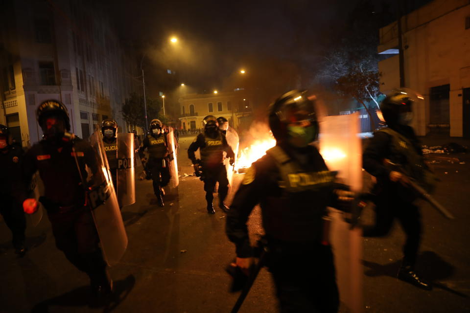 Police walk past burning barricades in order to take position to disperse protesters, near Congress where lawmakers swore-in a new president after voting to oust President Martin Vizcarra the day before, in Lima, Peru, Tuesday, Nov. 10, 2020. Peru swore in businessman and head of Congress Manuel Merino Tuesday who is unknown to most and was recently accused of trying to secure the military's support for a congressional effort to boot the nation's last leader out over unproven corruption allegations. (AP Photo/Rodrigo Abd)