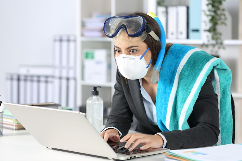 Anxious executive woman with protective mask booking vacation on laptop at the office with goggles and towel