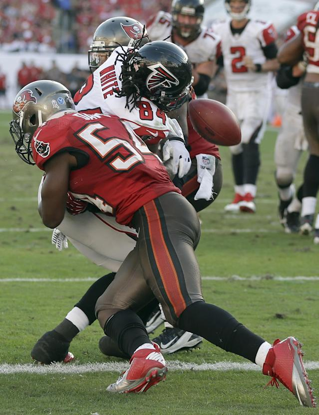 Atlanta Falcons wide receiver Roddy White (84) fumbles as he is sandwiched by Tampa Bay Buccaneers outside linebacker Lavonte David (54) and strong safety Mark Barron (23) during the fourth quarter of an NFL football game Sunday, Nov. 17, 2013, in Tampa, Fla. Officials ruled that White broke the end zone plane to score a touchdown. (AP Photo/Chris O'Meara)