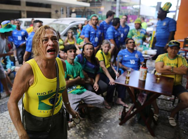 A Brazil soccer fans reacts as she watch on TV a goal scored against their team during the World Cup round of 16 match against Chile on a sidewalk at the Copacabana area, in Rio de Janeiro, Brazil, Saturday, June 28, 2014. (AP Photo/Leo Correa)