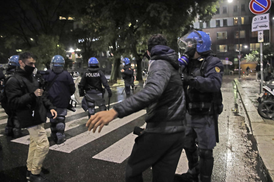 A police officer confronts a man during a protest against the government restriction measures to curb the spread of COVID-19, in Milan Italy, Monday, Oct. 26, 2020. Italy's leader has imposed at least a month of new restrictions to fight rising coronavirus infections, shutting down gyms, pools and movie theaters and putting an early curfew on cafes and restaurants. (AP Photo/Luca Bruno)
