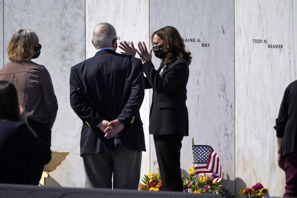 Vice President Kamala Harris, center, gestures as she visits with Ed Root, second from left, who is the cousin of Flight 93 passenger Lorraine G. Bay, and his daughter Emily, as they stand in front of Lorraine G Bay's stone on the Wall of Names at the Flight 93 National Memorial on Sept. 11, 2021 in Shanksville, Pa. (AP Photo/Gene J. Puskar)