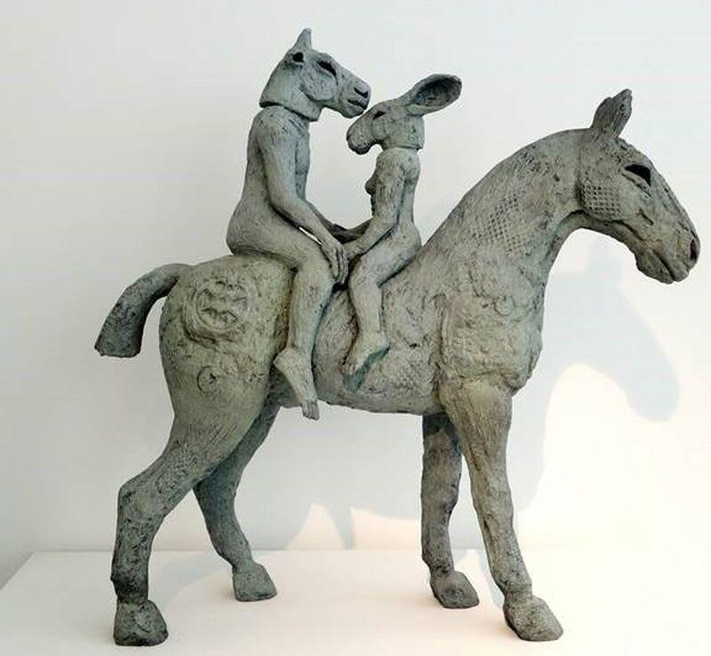 A sculpture of two animal-faced humans riding a horse.