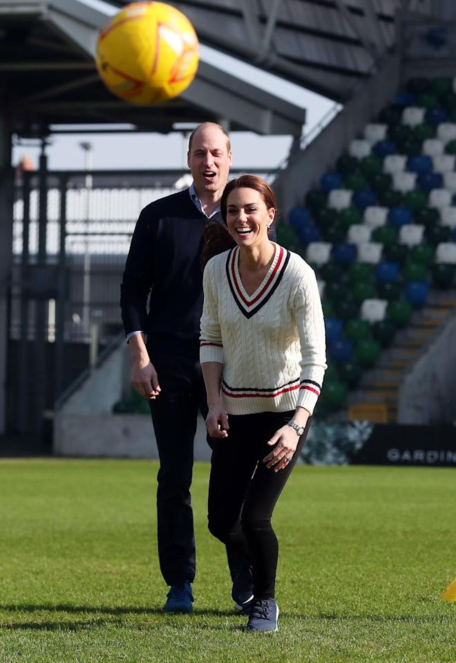 """<p><em>February 27, 2019</em> — Kate Middleton let loose with Prince William on a visit to the National Stadium in Belfast, Northern Ireland. The Duchess of Cambridge opted for a cute, cable-knit <a href=""""https://www.ralphlauren.com/women-clothing-sweaters/pink-pony-cricket-sweater/452708.html"""" target=""""_blank"""">Ralph Lauren sweater</a> and <a href=""""https://www.amazon.com/dp/B01LX3SA4S"""" target=""""_blank"""">New Balance sneakers</a>, and earlier a <a href=""""https://shop.nordstrom.com/s/barbour-hirsel-chevron-quilted-sweater-jacket/5042127"""" target=""""_blank"""">navy Barbour quilted jacket</a>, for kicking around a soccer ball with two youth charities. </p>"""