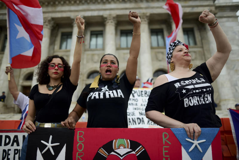 Women join a protest organized by Puerto Rican singer Rene Perez of Calle 13 over emergency aid that until recently sat unused in a warehouse amid ongoing earthquakes, in San Juan, Puerto Rico, Thursday, Jan. 23, 2020. Protesters demanded the ouster of Gov. Wanda Vázquez. (AP Photo/Carlos Giusti)