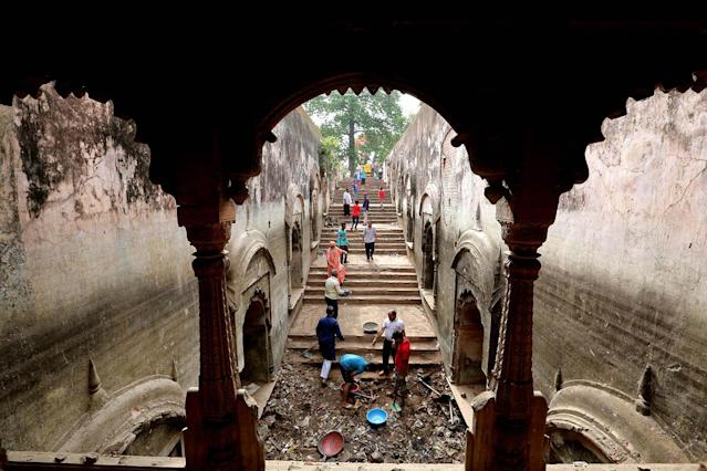 <p>Social workers clean during a cleanliness campaign at the historical, Bada Bagh Bawdi in Bhopal, India, May 12, 2017. Bada Bagh Bawdi is a historical pond built during the rule of Bhopal Nawab ruler, Qudsia Begum who ruled between 1819 to 1837. (Photo: Sanjeev Gupta/EPA) </p>