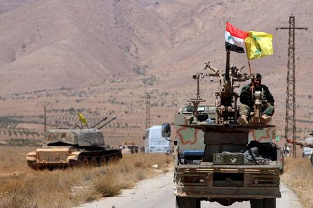 FILE PHOTO: Hezbollah and Syrian flags flutter on a military vehicle in Western Qalamoun