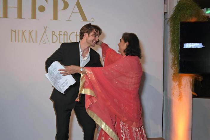 Robert Pattinson and former HFPA President Meher Tatna move in to hug each other