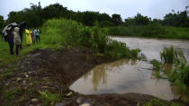 In this image made from video, people look at level of Canovanas river following heavy rain caused by the storm in Alto Trujillo, Puerto Rico, Thursday, July 30, 2020. Tropical Storm Isaias knocked out power and caused flooding and small landslides across Puerto Rico and the Dominican Republic on Thursday as forecasters predicted it would strengthen into a hurricane while moving toward the Bahamas and U.S. East Coast.(AP Photo)
