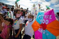 Children hold kites as the Petare neighbourhood celebrates the 400th anniversary of its founding, in Caracas