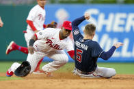 Philadelphia Phillies shortstop Jean Segura, left, tags out Atlanta Braves' Freddie Freeman, right, who was trying to steal second base during the third inning of a baseball game, Friday, July 23, 2021, in Philadelphia. (AP Photo/Chris Szagola)