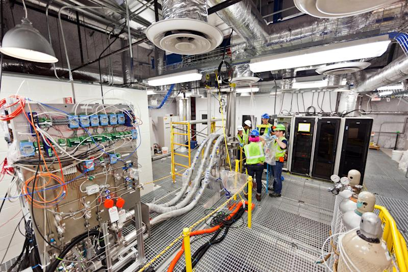 In this July 31, 2012 photo provided by Sanford Lab researchers work on the top floor of the Large Underground Xenon experiment at a shuttered gold mine in Lead, S.D.  The experiment, known as LUX, could begin collecting data on dark matter as early as February _ and, if all goes as planned, that data could answer age-old questions about the universe and its origins, scientists said Monday, Nov. 19, 2012. (AP Photo/Courtesy Sanford Lab, Matt Kapust)