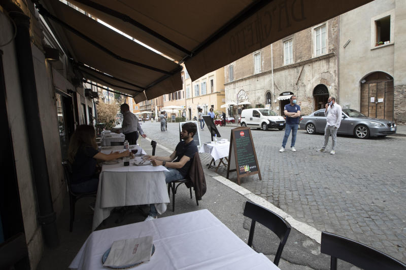 Customers have a lunch in a restaurant in downtown Rome, Monday, May 18, 2020 as Italy is slowly lifting sanitary restrictions after a two-month coronavirus lockdown. (AP Photo/Alessandra Tarantino)