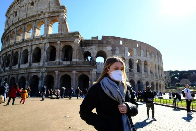 Tourist wearing a protective respiratory mask tours outside the Colosseo monument in downtown Rome on February 28, 2020 amid fear of Covid-19 epidemic. (ANDREAS SOLARO/AFP via Getty Images)