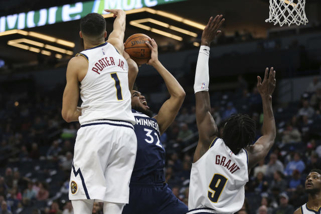 Minnesota Timberwolves' Karl-Anthony Towns shoots the ball against Denver Nuggets' Michael Porter Jr. and Jerami Grant in the first half of an NBA basketball game Monday, Jan. 20, 2020, in Minneapolis. (AP Photo/Stacy Bengs)