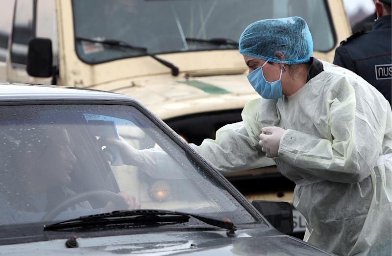 ARMAVIR PROVINCE, ARMENIA - MARCH 16, 2020: A medical worker measures the temperature of a car driver at an entrance to the city of Vagharshapat (Ejmiatsin) as part of the measures taken to prevent the spread of the COVID-19 coronavirus. Hayk Baghdasaryan/Photolure/TASS (Photo by Hayk Baghdasaryan\TASS via Getty Images)