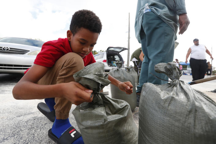 Isaiah Elie, 11, helps tie sandbags as his family fills them in preparation for Hurricane Dorian, Friday, Aug. 30, 2019, in Hallandale Beach, Fla., as the town allowed residents to fill up sandbags until they ran out. All of Florida is under a state of emergency and authorities are urging residents to stockpile a week's worth of food and supplies as Hurricane Dorian gathers strength and aims to slam the state as soon as Monday as a Category 4 storm. (AP Photo/Wilfredo Lee)
