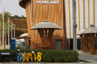"""Workers take a break near the Hungary pavilion at Expo 2020 in Dubai, United Arab Emirates, Sunday, Oct. 3, 2021. Dubai's Expo 2020 on Saturday, Oct. 2, 2021, offered conflicting figures for how many workers had been killed on site during construction of the massive world's fair, first saying five and then later three. In a later statement, Expo apologized and described the initial figure as a """"mistake."""" (AP Photo/Jon Gambrell)"""