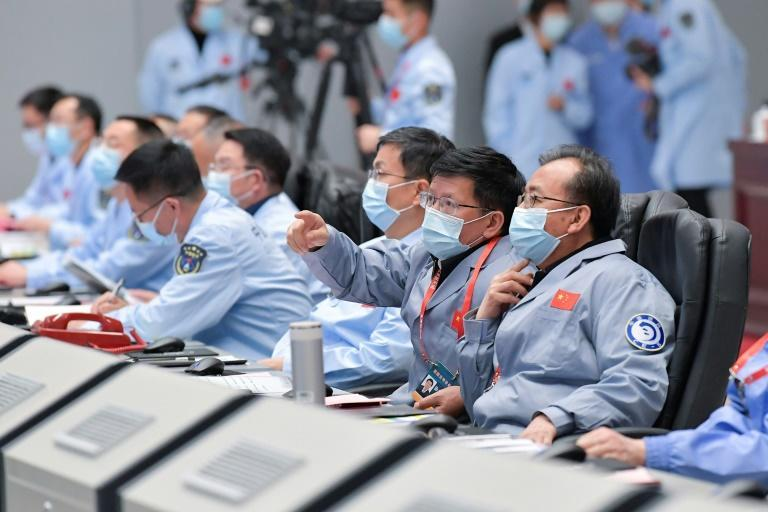 Technical personnel monitor the Chang'e-5 lunar probe landing on the moon from the Beijing Aerospace Control Center in Beijing