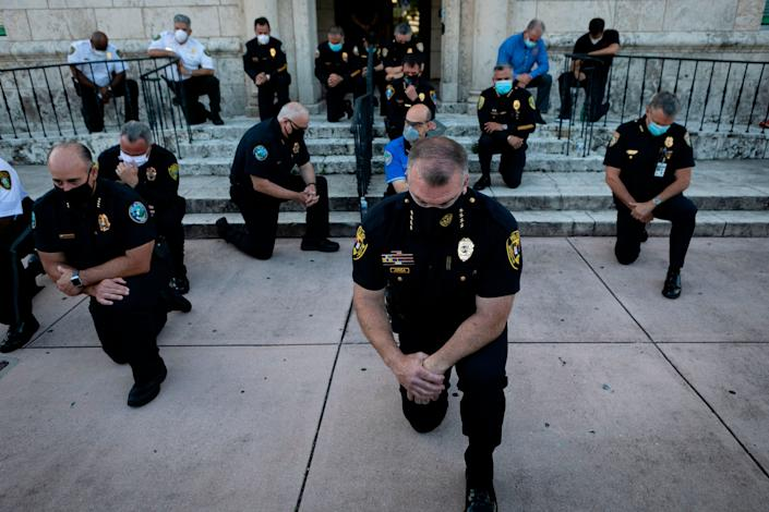Police officers kneeling in Coral Gables, Florida, on May 30.