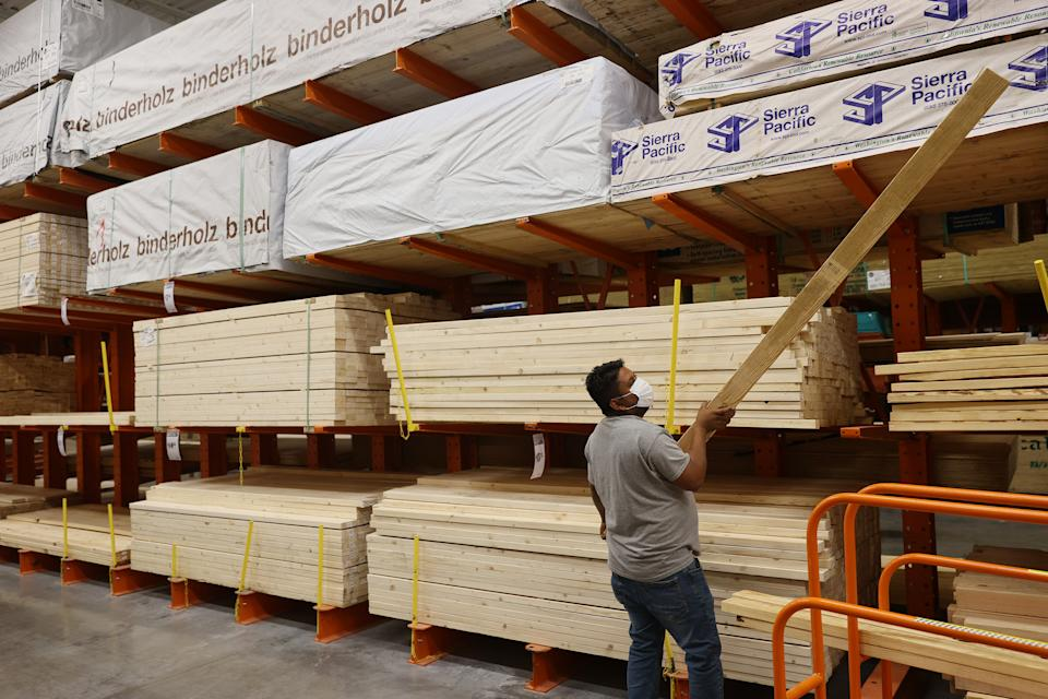 DORAL, FLORIDA - MAY 27: Enrique Matamoros shops for lumber at a Home Depot store on May 27, 2021 in Doral, Florida. According to the National Association of Home Builders, lumber prices went up 300% last year. Factors driving the price increase are more demand and growing production, labor, and transportation costs.  (Photo by Joe Raedle/Getty Images)