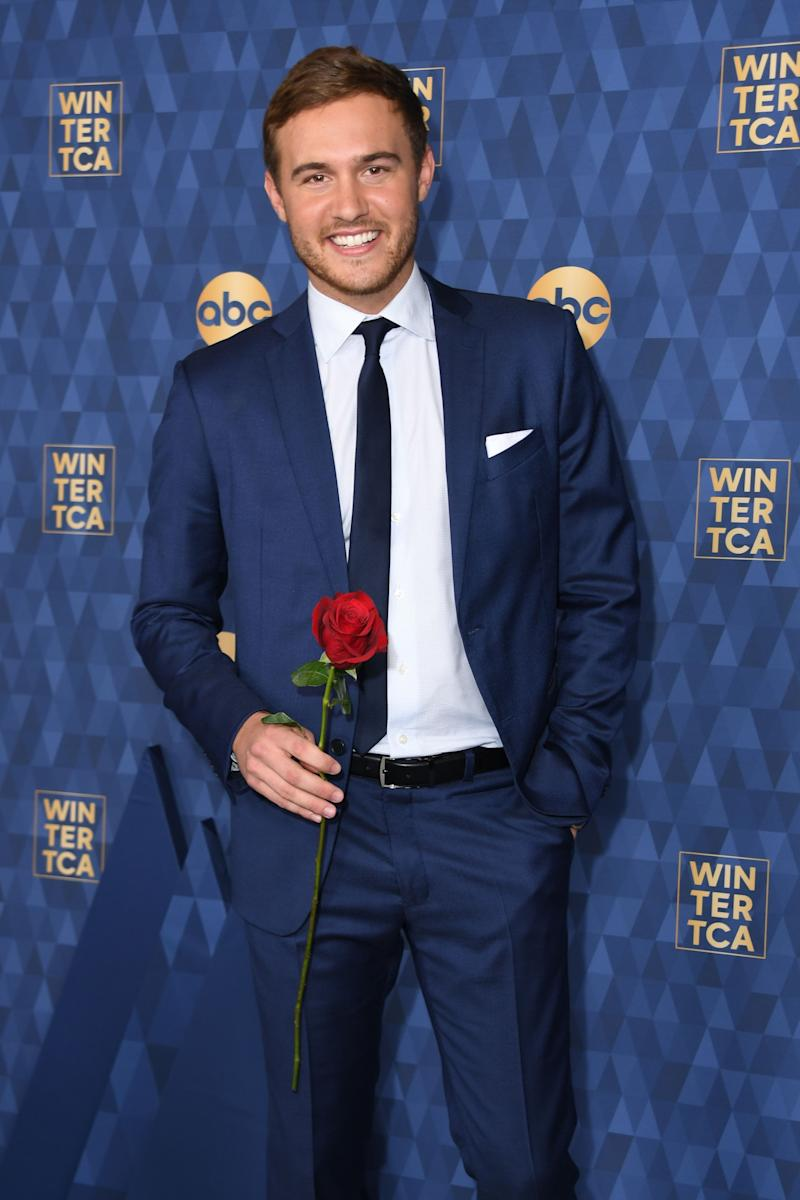 Peter Weber poses smiling holding a rose