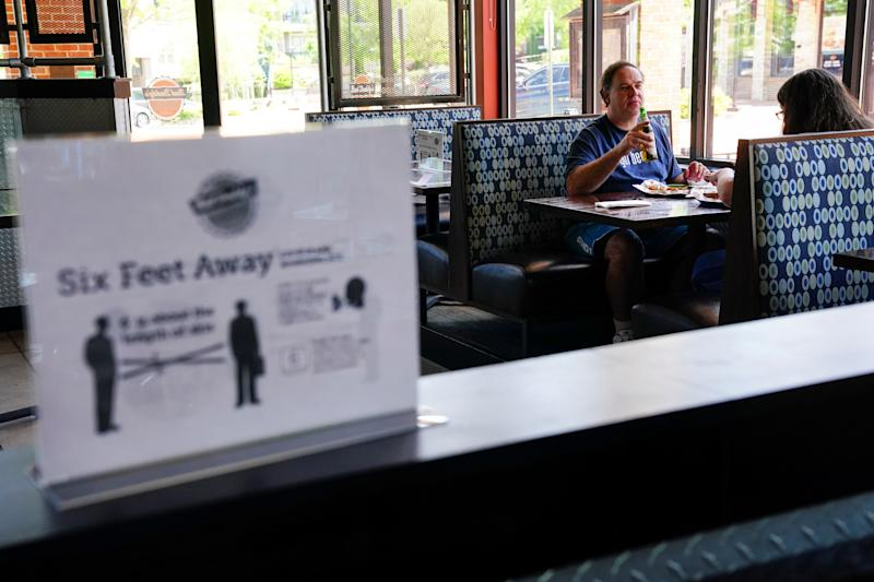 Customers eat lunch near a social distancing sign at Bad Daddy's Burger Bar on the day restaurants and theaters were allowed to reopen to the public as part of the phased reopening of businesses and restaurants from the coronavirus disease (COVID-19) restrictions in Smyrna, Georgia on April 27, 2020. (Elijah Nouvelage/Reuters)