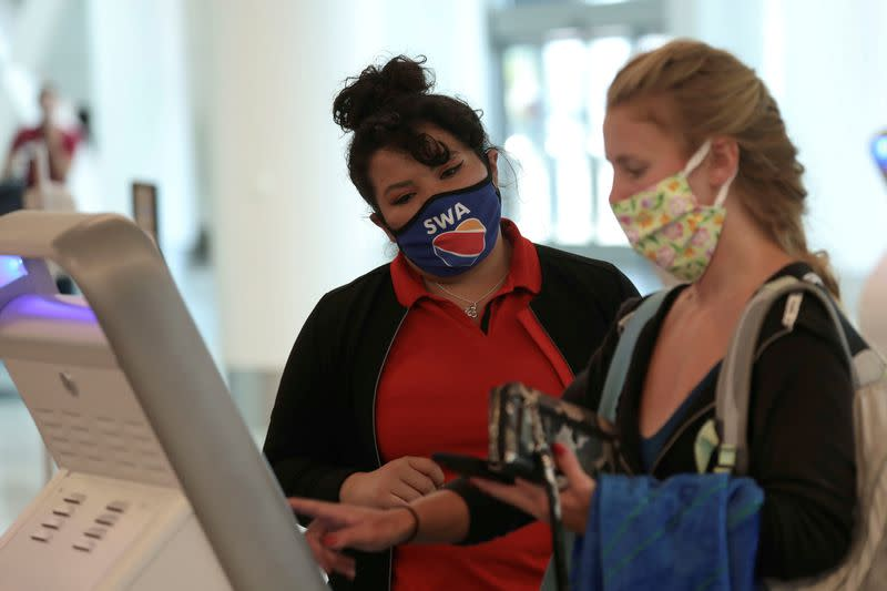 FILE PHOTO: A Southwest Airlines Co. employee wears a protective mask while assisting a passenger at Los Angeles International Airport (LAX) on an unusually empty Memorial Day weekend during the outbreak of the coronavirus disease (COVID-19) in Los Angeles