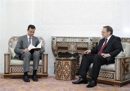 Syria's President Assad reads a message from Russian President Medvedev, during his meeting with Russian Deputy FM Bogdanov in Damascus