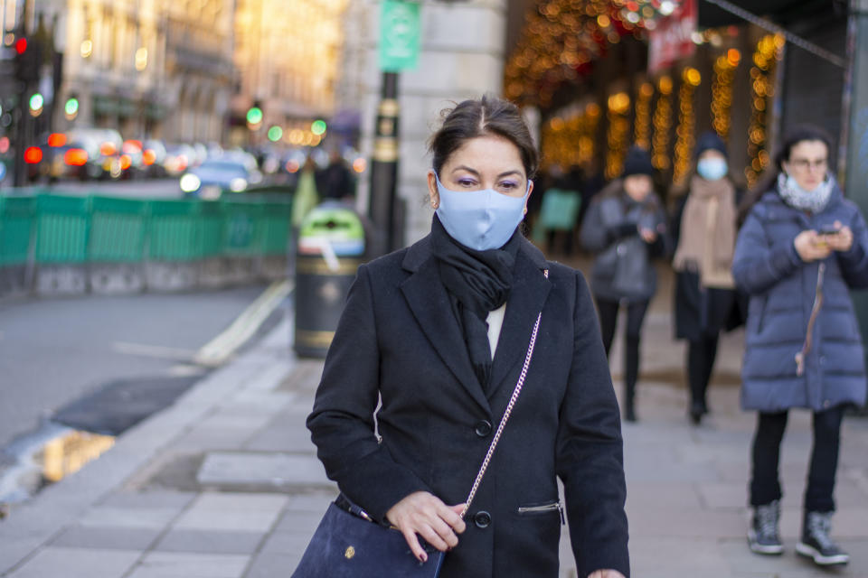 A lady wearing a face mask as preventive measure against the spread of covid 19 walks in Green Park. Under tier four restrictions, pubs and restaurants will close, as well as �non-essential� retail. (Photo by Pietro Recchia / SOPA Images/Sipa USA)