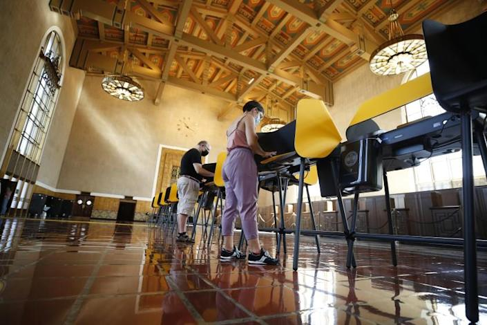 LOS ANGELES, CA - SEPTEMBER 13: Josh Hodas, left, and partner Serena Delgadillo, right, are among people casting their votes Monday morning in the historic Los Angeles Union Station Ticket Hall or Main Concourse built in 1939 as the largest railroad passenger terminal in the Western United States. The Union Station Hall is serving as a Vote Center for the recall effort against California Governor Gavin Newsom. Union Station on Monday, Sept. 13, 2021 in Los Angeles, CA. (Al Seib / Los Angeles Times).