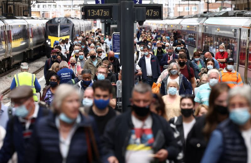 People wearing protective face masks walk along a platform at King's Cross Station, amid the coronavirus disease (COVID-19) outbreak in London