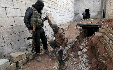 A Turkish-backed Syrian rebel helps his fellow rebel in the town of Tadef in Aleppo Governorate - Credit: REUTERS