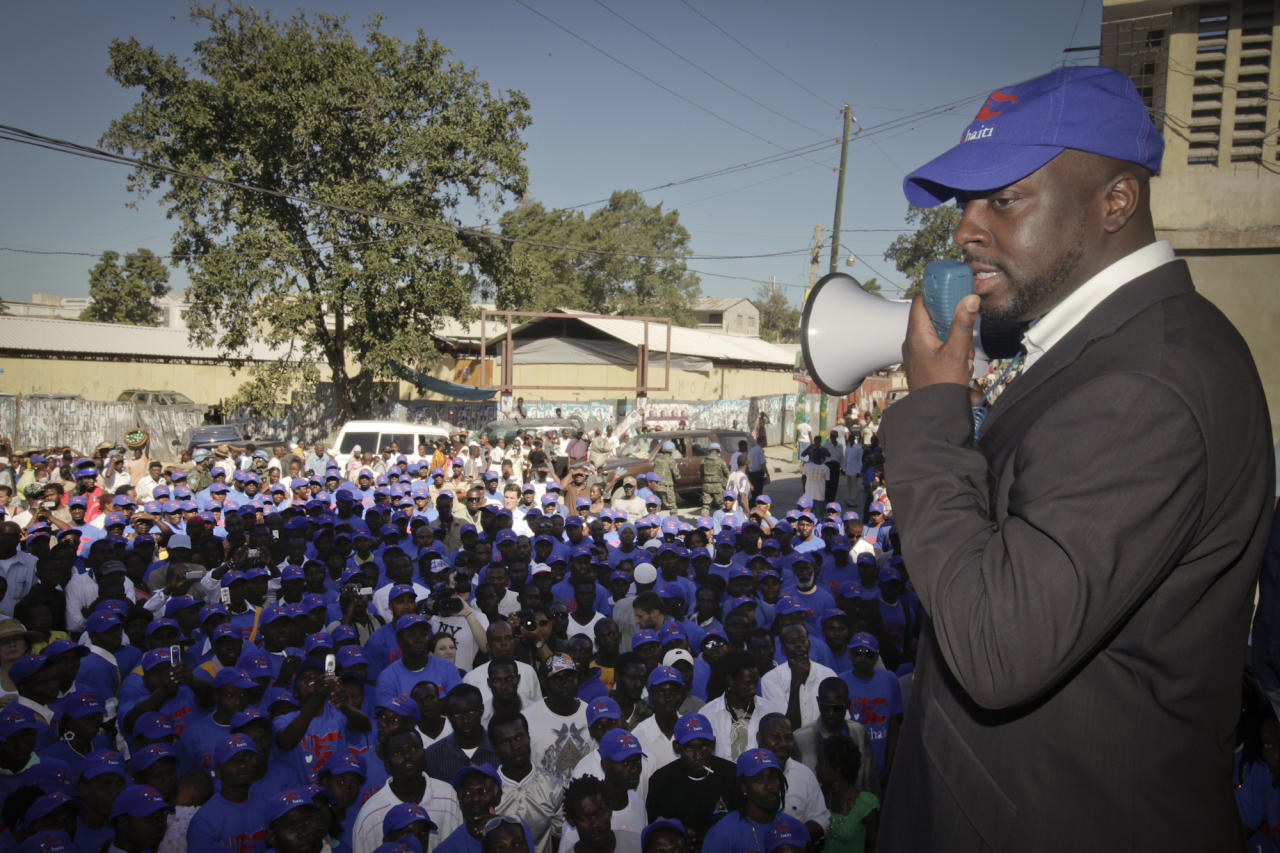 In this photo provided by Yele Haiti, singer Wyclef Jean speaks to Yele Corps workers following a church service commemorating the anniversary of last year's earthquake in Port Au Prince, Haiti, Wednesday, Jan. 12, 2011. Yele Corps employs 2000 Haitians a day cleaning streets and canals.