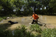 Dustin Shadownes, of Ashland City Fire Department, searches a creek for missing persons along with a cadaver dog, Monday, Aug. 23, 2021, in Waverly, Tenn. Heavy rains caused flooding in Middle Tennessee days earlier, resulting in multiple deaths, missing persons and property destroyed. (AP Photo/John Amis)
