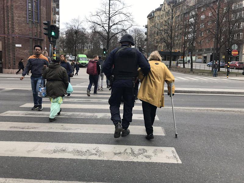 The image of the armed police officer leading an elderly lady across the road by the scene of the Stockholm attack has caught the imagination of Twitter: Frida Sundkvist, Twitter