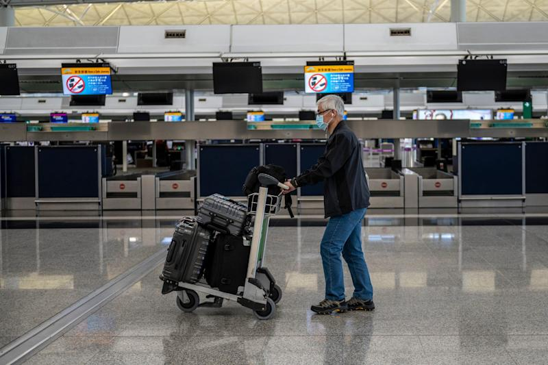 A Man with a luggage trolley Is seen walking pass empty check in counters inside the terminal of the Hong Kong International Airport on February 22, 2020 in Hong Kong, China. 2