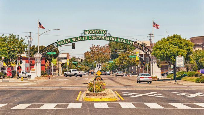 Modesto, California, USA - May 15, 2016: This Arch with the name and mottos of the City Welcomes visitors to Modesto in the Central Valley of Northern California, the arch defines the feelings of the population that enjoys calling this home, the many signs and flags and vehicles make this entrance to this sections of this city very interesting and within close distance of historic site and museum this is also the setting for a very classic movie American Graffiti, areas of the city reflect the memories of the 1950's and on this May day it was very comfortable and interesting.