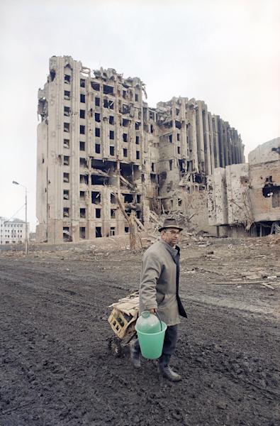 FILE - In this Feb. 17, 1995 file photo, a resident of Grozny carries a water bucket and some personal belongings past the battered presidential palace in Grozny, Chechnya, Russia. Two suspects in the Boston Marathon bombing have been identified to The Associated Press as coming from a Russian region near Chechnya. In the past, insurgents from Chechnya and neighboring restive provinces in the Caucasus have been involved in terror attacks in Moscow and other places in Russia. (AP Photo/Olga Shalygin, File)